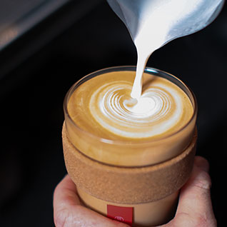 Milk being poured into coffee